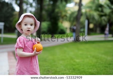Adorable toddler girl holding a big orange - stock photo