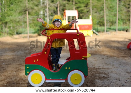 Adorable toddler girl in yellow rain coat playing on playground in playground car - stock photo