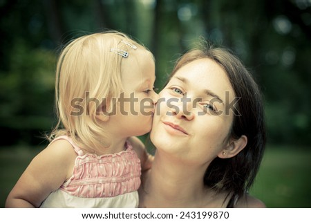 Adorable toddler girl kissing her Mom in the park. Big smile. Summer Colorful natural light - stock photo
