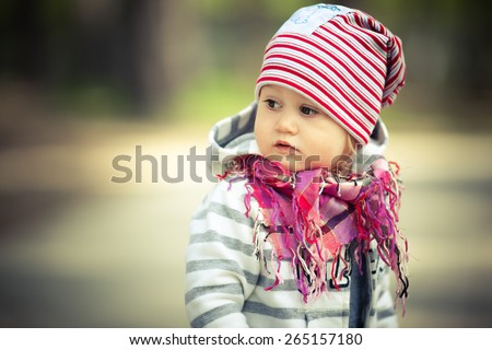 Adorable toddler girl looking somewhere. Bright scarf and hat. Stripes on her clothes. - stock photo