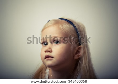 Adorable toddler girl looking up in front of the camera.