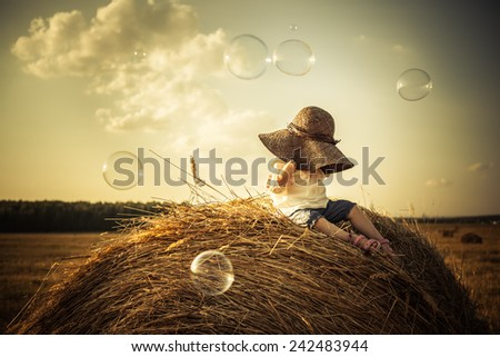 Adorable toddler girl on the haystack the last thing in hats. Face closed. Poke bonnet. Bubbles. Soft sunset light. - stock photo