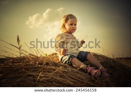Adorable toddler girl on the haystack the. Soft sunset light. - stock photo