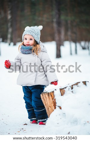 adorable toddler girl on the walk in winter snowy forest - stock photo