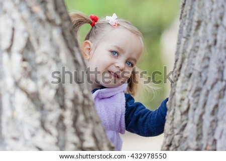 Adorable toddler girl playing hide and seek (pick a boo) game behind trees. Child in spring park looking straight to the camera. Natural light conditions, selective focus. - stock photo