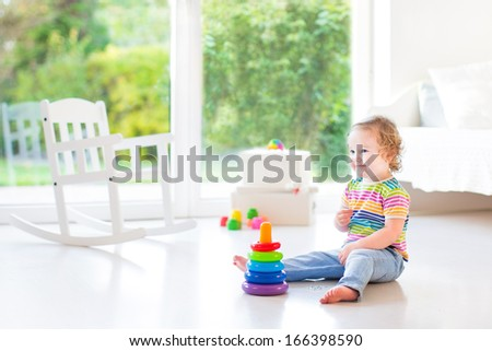 Adorable toddler girl playing in a beautiful white room with a big window with garden view - stock photo