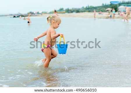 Adorable toddler girl playing with beach toys on white sand beach
