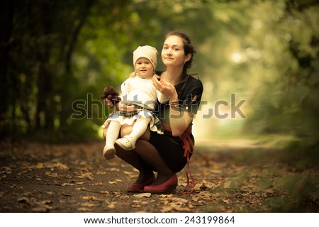 Adorable toddler girl playing with fashion Mom in the park. Autumn. Magic beauty natural back light - stock photo