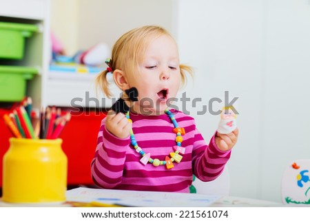 Adorable toddler girl playing with finger puppets at home or daycare - stock photo