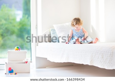 Adorable toddler girl reading a book sitting on a white bed next to a big window - stock photo