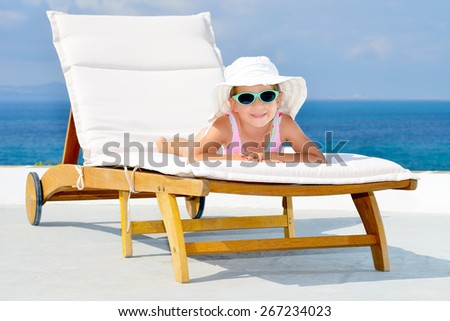 Adorable toddler girl relaxing on sunbed