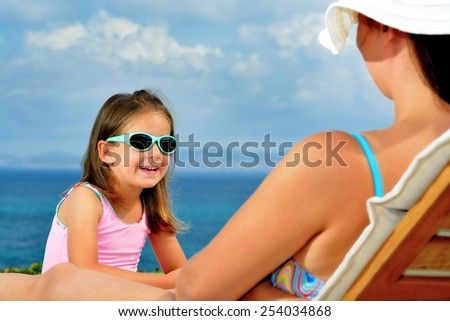 Adorable toddler girl relaxing on sunbed with her mother - stock photo