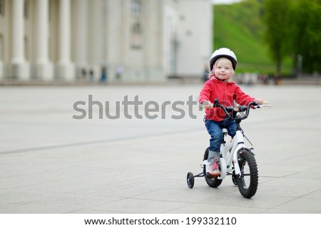 Adorable toddler girl riding her first bike - stock photo