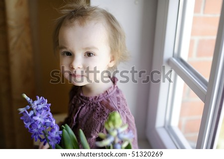 Adorable toddler girl sitting by the window with the flowers