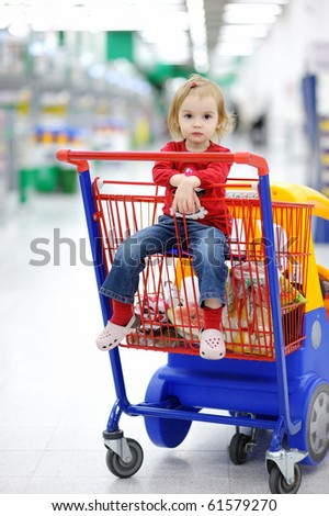 Adorable toddler girl sitting in shopping cart - stock photo