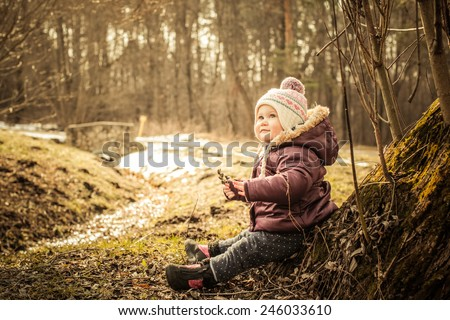 Adorable toddler girl sitting on the ground in the park. Cold spring - stock photo