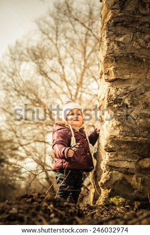 Adorable toddler girl staying near the wall of rocks in the park. Cold spring - stock photo
