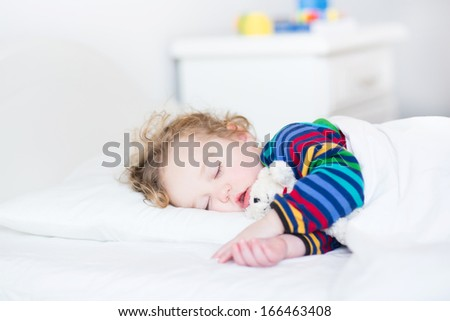 Adorable toddler girl taking a nap in a white bed holding her teddy bear - stock photo