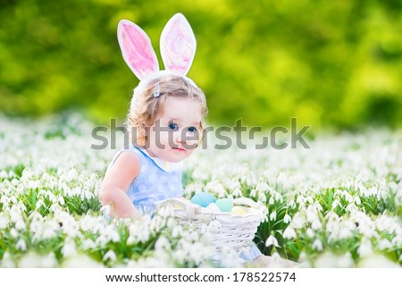 Adorable toddler girl wearing bunny ears playing with Easter eggs in a white basket sitting in a sunny garden with first white spring flowers - stock photo