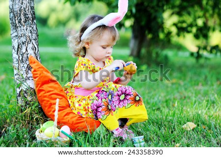 Adorable toddler girl wearing bunny ears playing with Easter eggs  sitting in a sunny garden  - stock photo