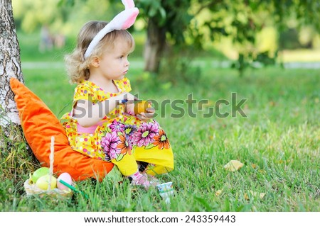 Adorable toddler girl wearing bunny ears playing with Easter eggs  sitting in a sunny garden