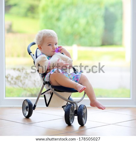 Adorable toddler girl with blond curly hair playing indoors with puppy toy sitting in the doll stroller in white sunny room next to big garden view window