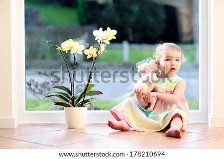 Adorable toddler girl with blond curly hair playing indoors with puppy toy sitting on tiles floor in white sunny room next to big street view window with beautiful orchid in the pot - stock photo