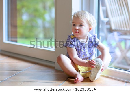 Adorable toddler girl with blonde curly hair putting on her shoe sitting on the tiles floor next to a big sliding door window with garden view getting ready to play outdoors - stock photo