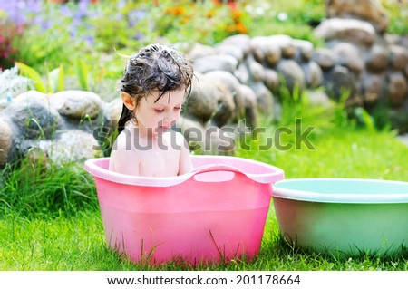 Adorable toddler girl with brunette hair having bath and playing with water in the pink washbowl outdoors  in the garden on the hot summer day