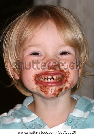adorable toddler girl with chocolate all over mouth - stock photo