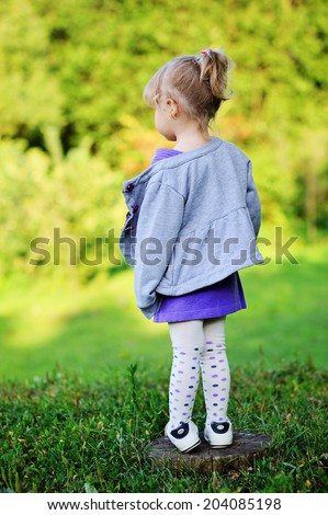 Adorable toddler girl with curly blond hair in knit purple dress and grey jacket playing outdoors on beauty sunny day - stock photo