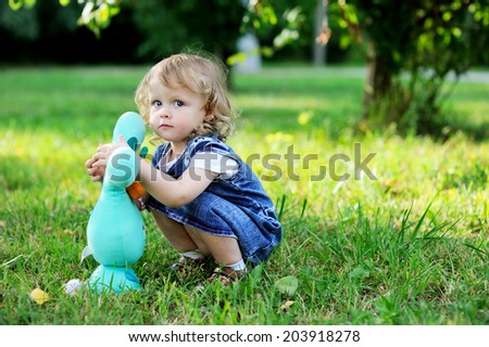 Adorable toddler girl with curly blond  hair wearing a jeans  dress playing  with toy rabbit outdoors in the summer park - stock photo