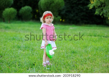 Adorable toddler girl with curly blond  hair wearing a red sailor dress playing with toy ship outdoors on beauty summer day   - stock photo