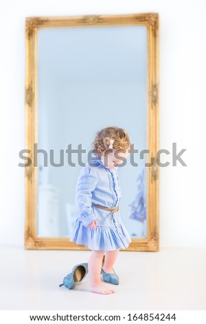 Adorable toddler girl with curly hair wearing a blue dress is trying to put on her mother's high heels shoes in a white bedroom in front of a big mirror