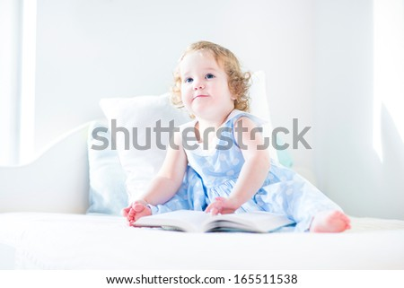 Adorable toddler girl with curly hair wearing a blue dress reading a book sitting on a white bed in a sunny bedroom - stock photo