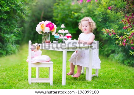 Adorable toddler girl with curly hair wearing a colorful dress on her birthday playing tea party with a teddy bear doll, toy dishes, cup cakes and muffins in a sunny summer garden - stock photo