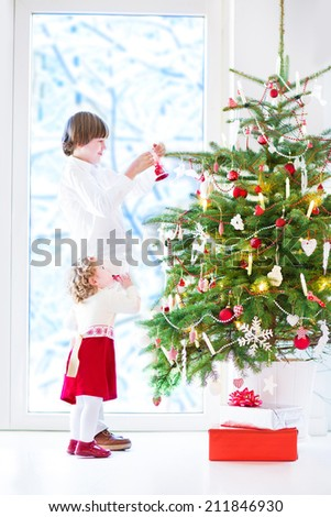 Adorable toddler girl with curly hair wearing a warm red dress helping her brother to decorate a beautiful Christmas tree standing next to a big window with a view of a snowy garden - stock photo