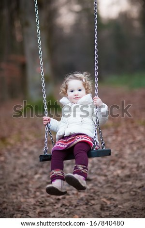 Adorable toddler girl with curly hair wearing a white warm jacket and purple dress having fun on a swing in a dark autumn park on a cold November day - stock photo