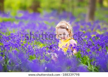Adorable toddler girl with curly hair wearing a yellow dress playing with purple bluebell flowers in a sunny spring forest on a warm evening with beautiful sunset - stock photo