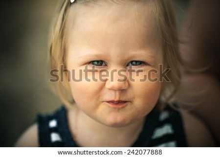 Adorable toddler girl with looking directly at the camera. Making funny face. Smiling.