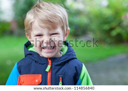 Adorable toddler in colorful autumn jacket outdoor