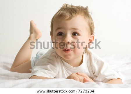 Adorable toddler lying on stomach, against white background