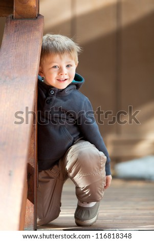 Adorable toddler playing hide and seek outside - stock photo
