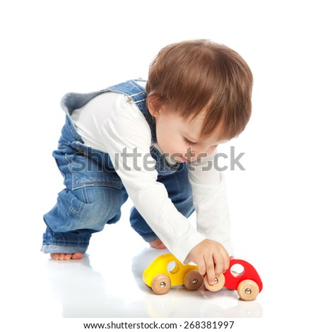 Adorable toddler playing with toy cars, isolated on white