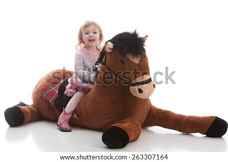 Adorable toddler riding a giant stuffed horse.  Isolated on white.
