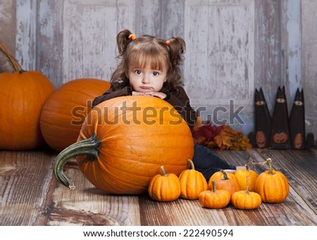 Adorable toddler sitting behind a giant pumpkin looking sad.   - stock photo