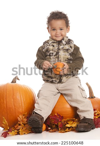 Adorable toddler sitting on a large pumpkin.  Isolated on white.
