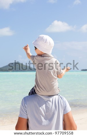 adorable toddler sitting on his father shoulders and showing the way - stock photo