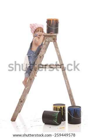 Adorable toddler surrounded by paint cans and climbing a ladder.  Isolated on white with room for your text. - stock photo