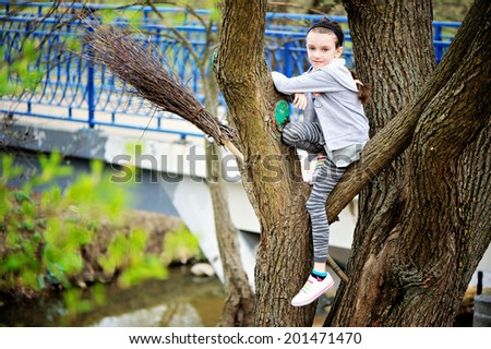 Adorable tween girl in the grey hoody and skirt and colorful sneakers climbing on the tree in the park - stock photo